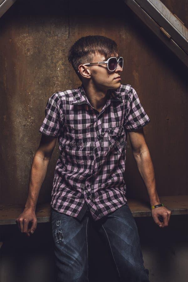 Νεαρός άνδρας πέρα από το βιομηχανικό υπόβαθρο στοκ εικόνες