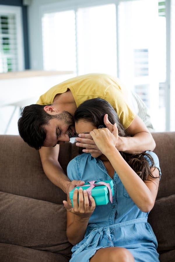 Νεαρός άνδρας που δίνει ένα αιφνιδιαστικό δώρο στη γυναίκα στο καθιστικό στοκ φωτογραφίες με δικαίωμα ελεύθερης χρήσης