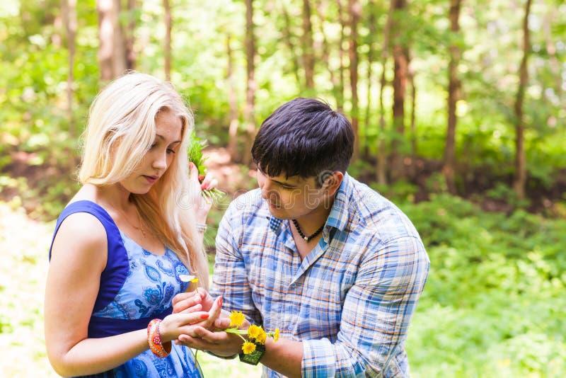 Νεαρός άνδρας που δίνει μια πικραλίδα λουλουδιών στη φίλη υπαίθρια στοκ εικόνες με δικαίωμα ελεύθερης χρήσης