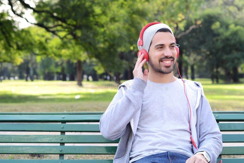 Νεαρός άνδρας που ακούει τη μουσική με τα ακουστικά που κάθονται στο πάρκο ben στοκ φωτογραφίες