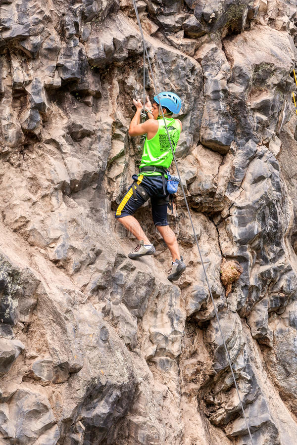 Νεαρός άνδρας που αναρριχείται σε έναν τοίχο ασβεστόλιθων στοκ εικόνες