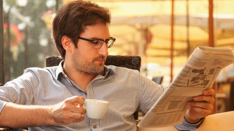Νεαρός άνδρας που απολαμβάνει στον καφέ στοκ φωτογραφία