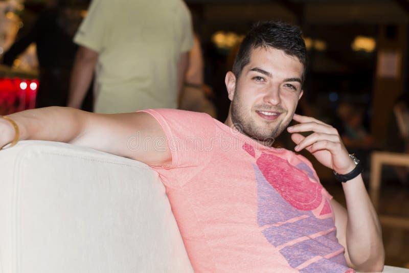 Νεαρός άνδρας που απολαμβάνει τις διακοπές σε έναν φραγμό νύχτας στοκ εικόνες
