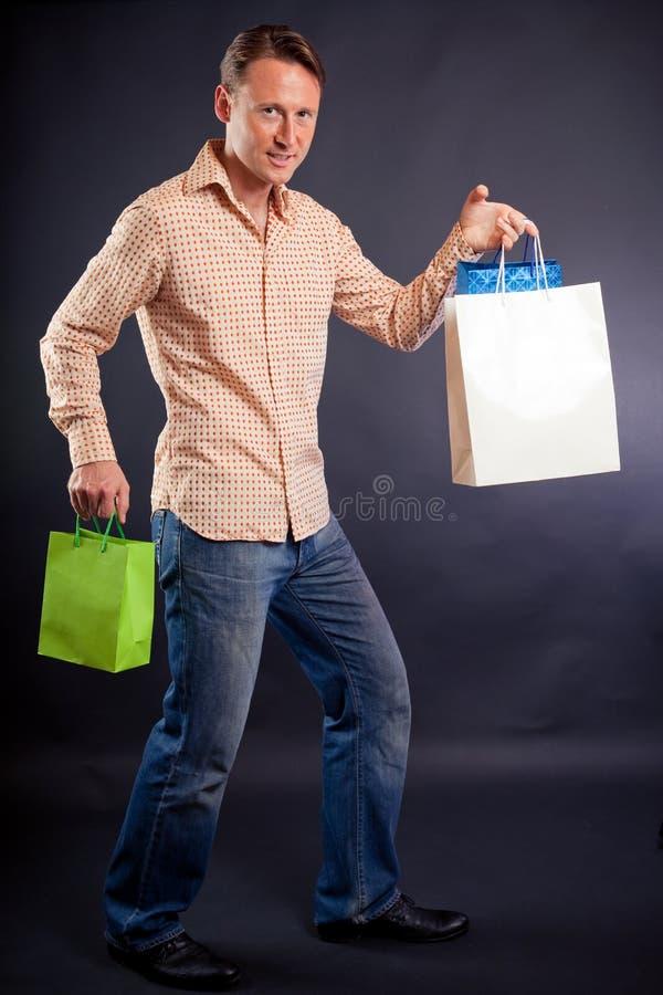Νεαρός άνδρας που απολαμβάνει το ξεφάντωμα αγορών του στοκ φωτογραφίες