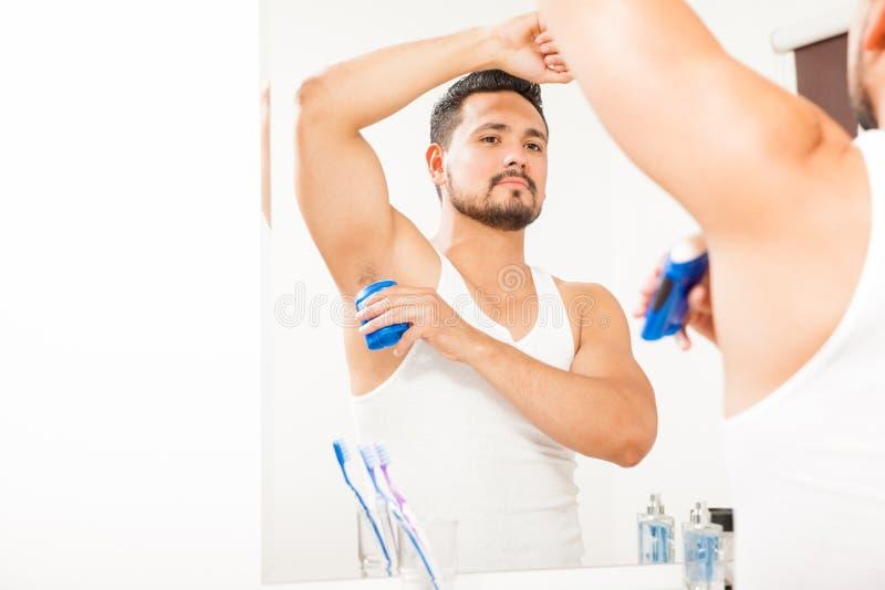 Νεαρός άνδρας που βάζει στο αποσμητικό στο λουτρό στοκ εικόνες με δικαίωμα ελεύθερης χρήσης