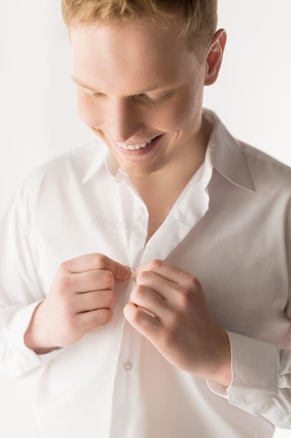 Νεαρός άνδρας που βάζει το άσπρο πουκάμισο επάνω στοκ εικόνες με δικαίωμα ελεύθερης χρήσης