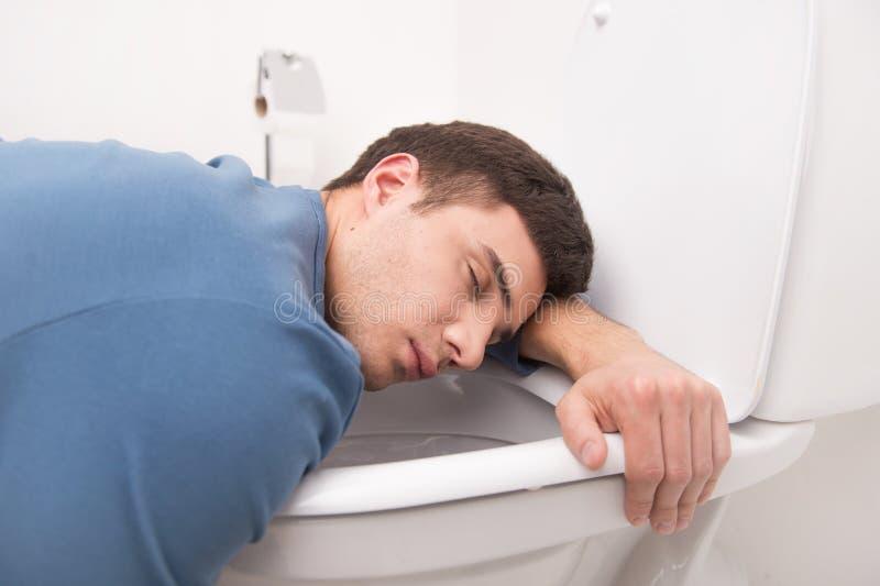 Νεαρός άνδρας που βρίσκεται στο κάθισμα τουαλετών στοκ εικόνες