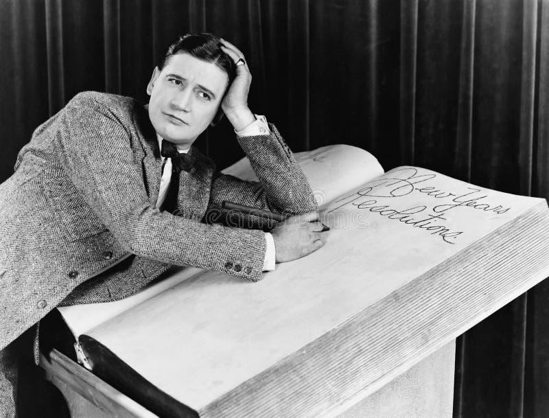 Νεαρός άνδρας που γράφει σε ένα μεγάλου μεγέθους βιβλίο σημειώσεων (όλα τα πρόσωπα που απεικονίζονται δεν ζουν περισσότερο και κα στοκ εικόνες