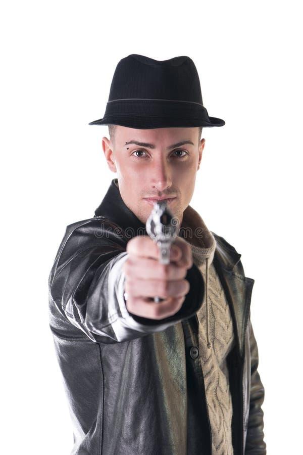 Νεαρός άνδρας που δείχνει το πυροβόλο όπλο στη κάμερα, που φορά το σακάκι καπέλων και δέρματος στοκ εικόνες με δικαίωμα ελεύθερης χρήσης