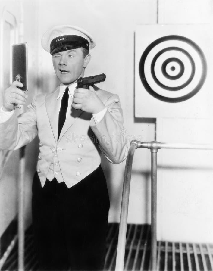 Νεαρός άνδρας που εξετάζει έναν καθρέφτη και που στοχεύει σε ένα dartboard με ένα περίστροφο (όλα τα πρόσωπα που απεικονίζονται δ στοκ εικόνες