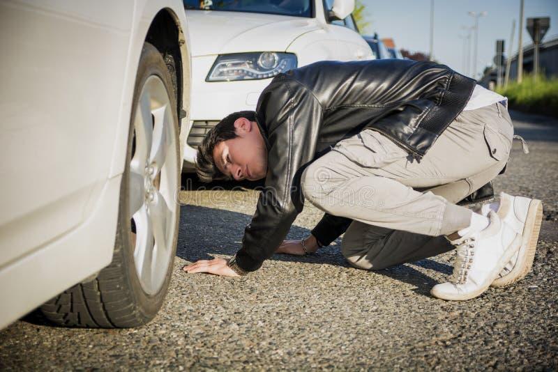 Νεαρός άνδρας που εξετάζει Underside του αυτοκινήτου στοκ εικόνες