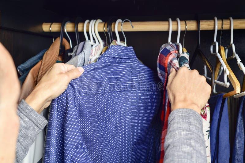 Νεαρός άνδρας που επιλέγει ένα πουκάμισο από ένα ράφι ενδυμάτων στοκ εικόνες