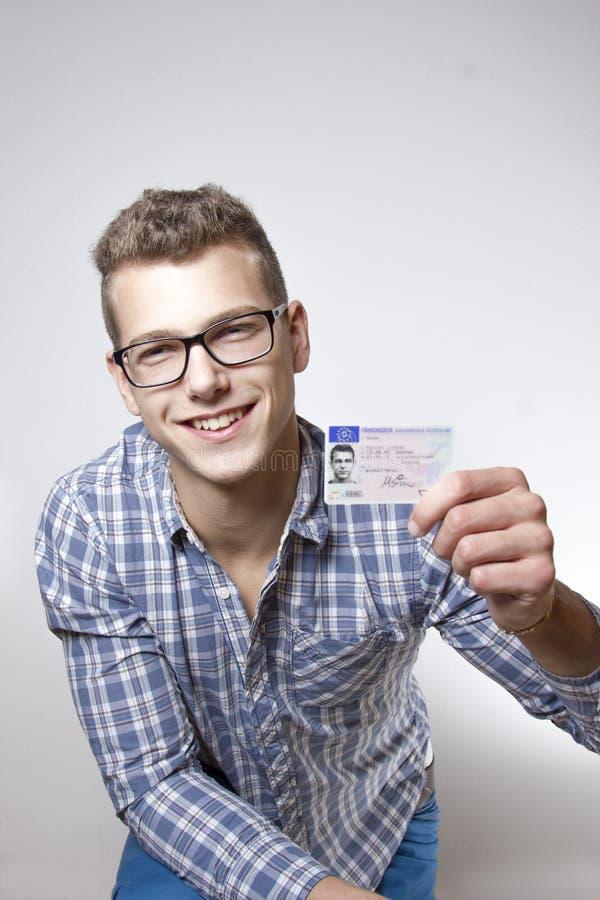 Νεαρός άνδρας που επιδεικνύει τη άδεια οδήγησης του στοκ εικόνα με δικαίωμα ελεύθερης χρήσης