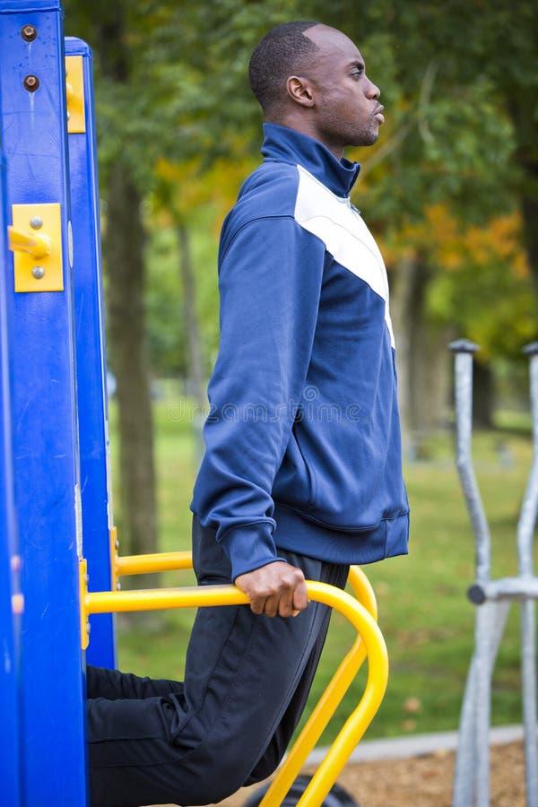Νεαρός άνδρας που επιλύει στην υπαίθρια γυμναστική στοκ φωτογραφία