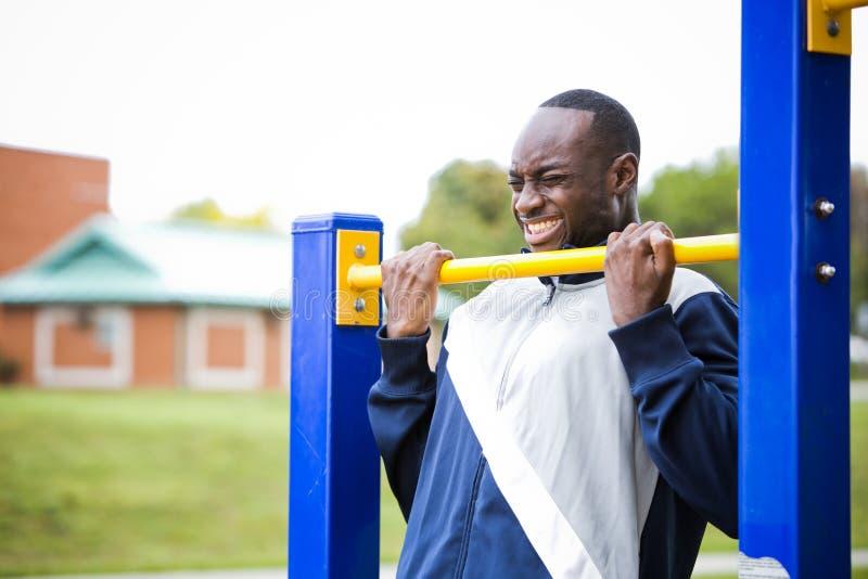 Νεαρός άνδρας που επιλύει στην υπαίθρια γυμναστική στοκ εικόνες