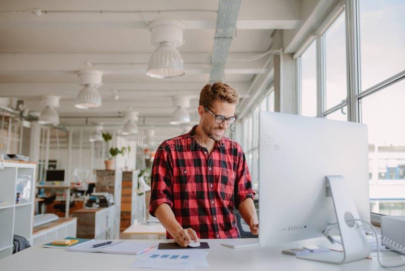 Νεαρός άνδρας που εργάζεται στο σύγχρονο εργασιακό χώρο στοκ εικόνες με δικαίωμα ελεύθερης χρήσης