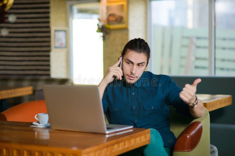 Νεαρός άνδρας που εργάζεται στο lap-top σε έναν καφέ στοκ φωτογραφίες με δικαίωμα ελεύθερης χρήσης
