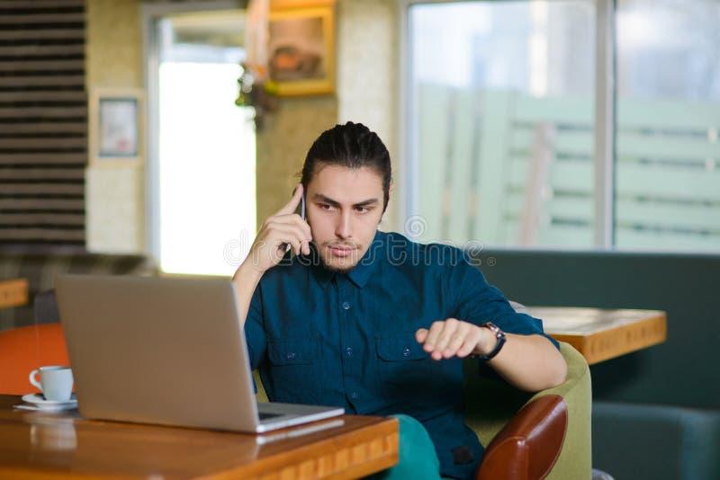 Νεαρός άνδρας που εργάζεται στο lap-top σε έναν καφέ στοκ εικόνα