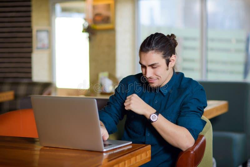Νεαρός άνδρας που εργάζεται στο lap-top σε έναν καφέ στοκ εικόνες