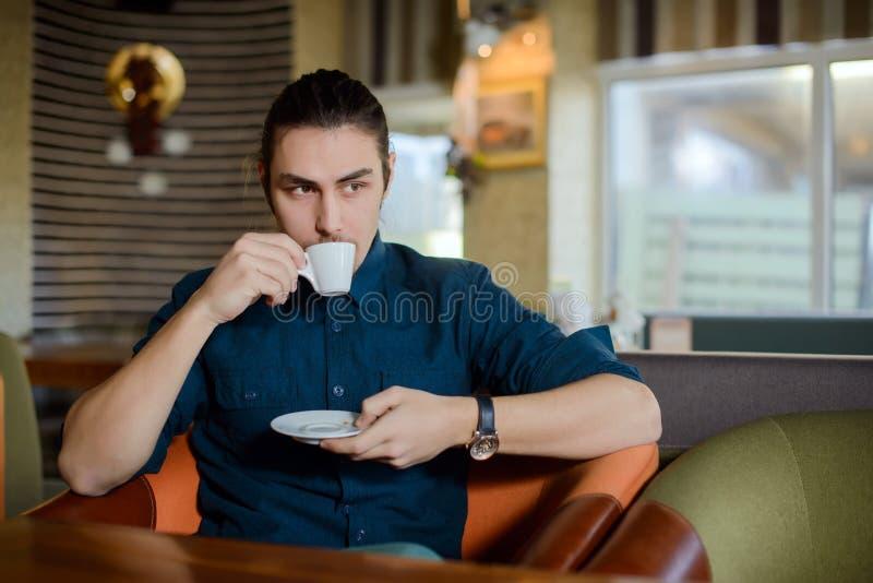 Νεαρός άνδρας που εργάζεται στο lap-top σε έναν καφέ στοκ εικόνες με δικαίωμα ελεύθερης χρήσης