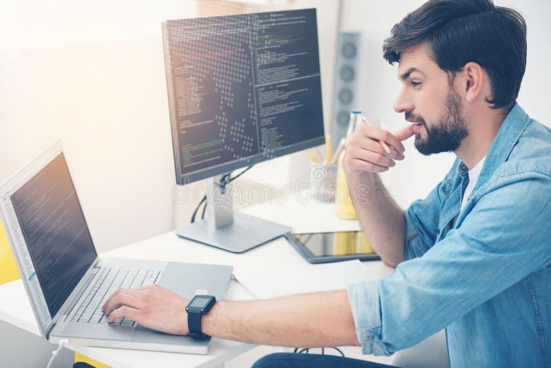 Νεαρός άνδρας που εργάζεται ως προγραμματιστής στοκ φωτογραφία