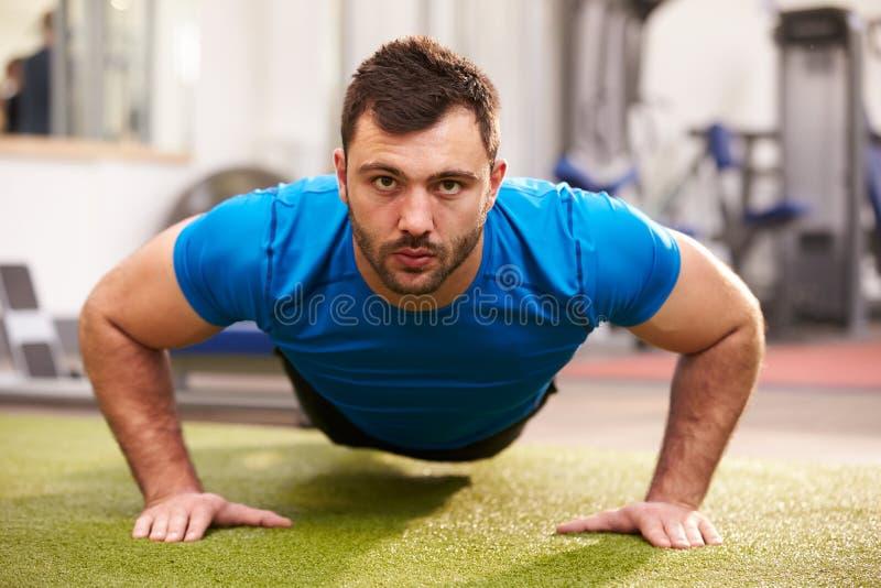 Νεαρός άνδρας που κάνει την ώθηση UPS σε μια γυμναστική, που κοιτάζει στη κάμερα στοκ φωτογραφία