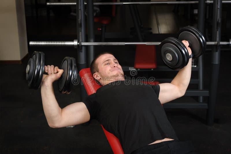 Νεαρός άνδρας που κάνει τον Τύπο πάγκων workout στη γυμναστική στοκ φωτογραφία