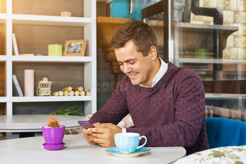 Νεαρός άνδρας που κρατά ένα κινητά τηλέφωνο και ένα χαμόγελο στοκ εικόνες