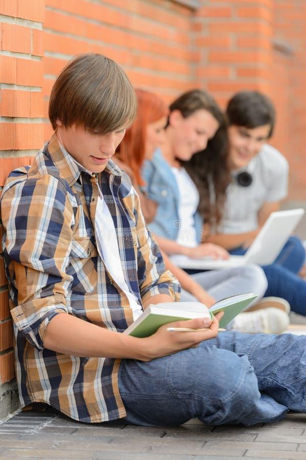 Νεαρός άνδρας που μελετά τους φίλους βιβλίων στο υπόβαθρο στοκ φωτογραφία
