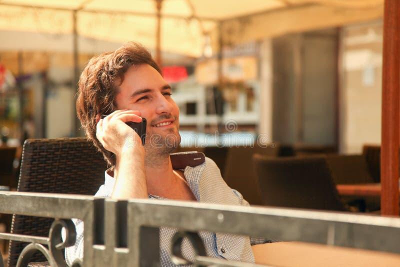 Νεαρός άνδρας που μιλά σε ένα κινητό τηλέφωνο στοκ εικόνα