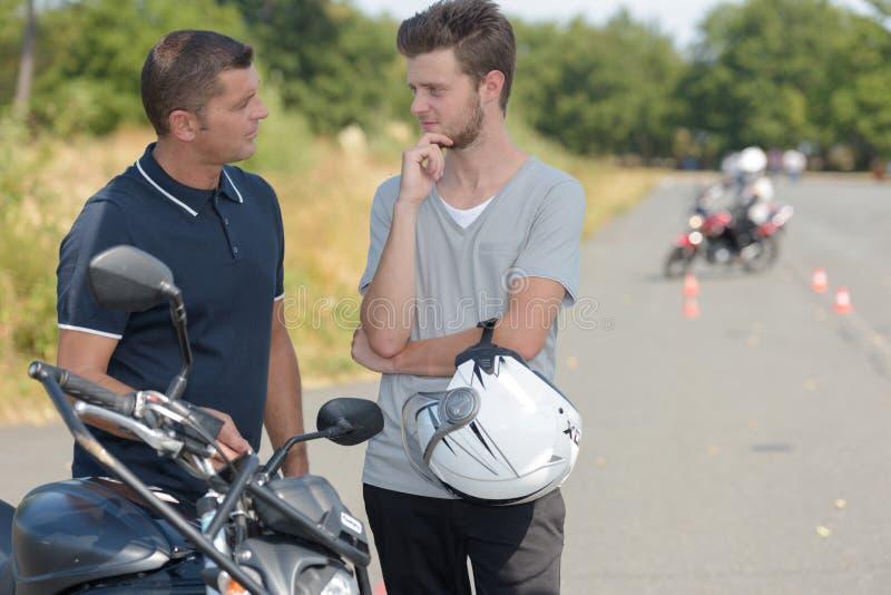 Νεαρός άνδρας που μιλά στο εκπαιδευτικό μάθημα μοτοσικλετών εκπαιδευτικών στοκ φωτογραφίες με δικαίωμα ελεύθερης χρήσης