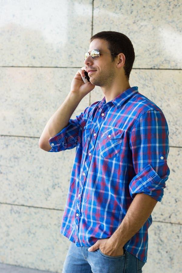 Νεαρός άνδρας που μιλά στο κινητό τηλέφωνο στοκ εικόνα με δικαίωμα ελεύθερης χρήσης