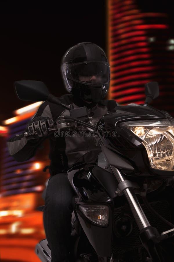 Νεαρός άνδρας που οδηγά μια μοτοσικλέτα τη νύχτα μέσω των οδών του Πεκίνου στοκ εικόνα
