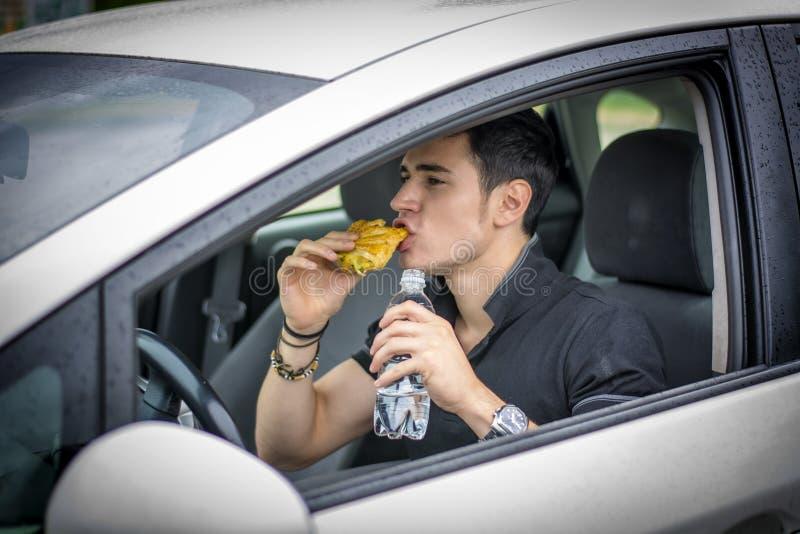Νεαρός άνδρας που οδηγεί το αυτοκίνητό του τρώγοντας τα τρόφιμα στοκ εικόνες