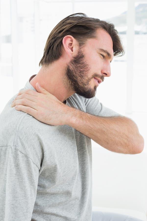 Νεαρός άνδρας που πάσχει από τον πόνο ώμων στοκ εικόνες