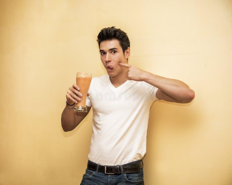 Νεαρός άνδρας που πίνει το μεγάλο ποτήρι των υγιών φρούτων στοκ εικόνες