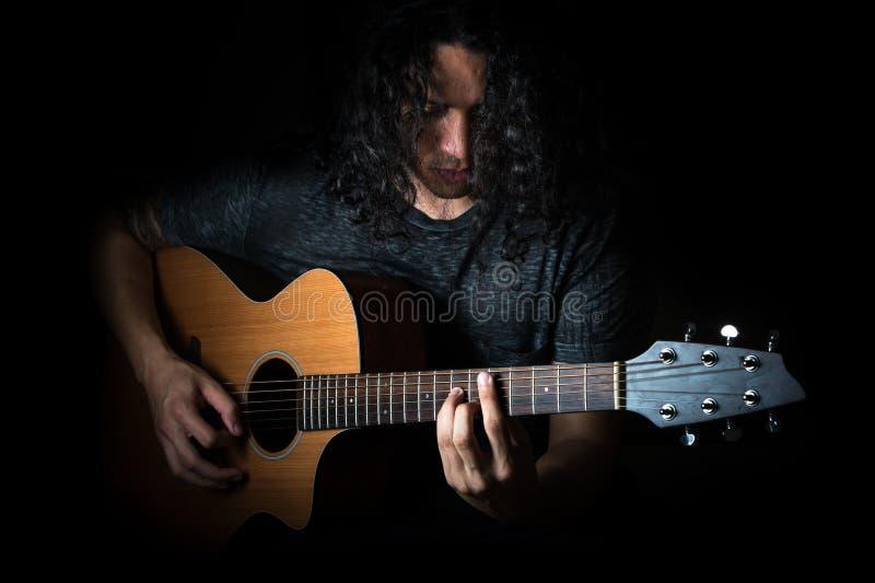 Νεαρός άνδρας που παίζει μια κιθάρα στοκ εικόνα με δικαίωμα ελεύθερης χρήσης
