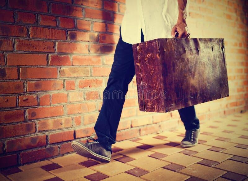 Νεαρός άνδρας που περπατά κατά μήκος της οδού με την παλαιά βαλίτσα, στοκ φωτογραφία με δικαίωμα ελεύθερης χρήσης