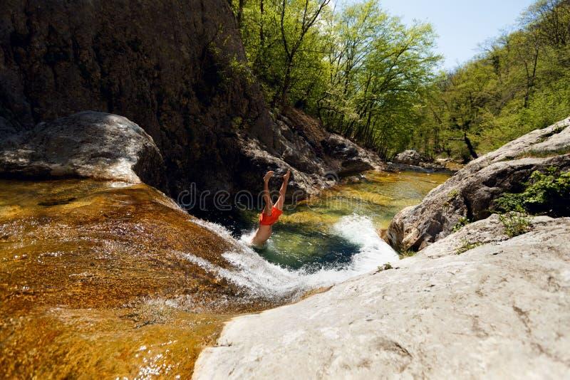 Νεαρός άνδρας που πηδά από τον απότομο βράχο στο νερό του ποταμού βουνών στοκ φωτογραφίες