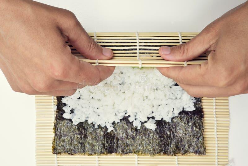 Νεαρός άνδρας που προετοιμάζει το makizushi στοκ εικόνα με δικαίωμα ελεύθερης χρήσης