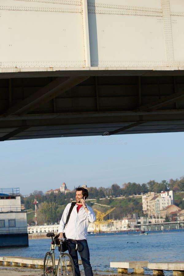 Νεαρός άνδρας που στέκεται έξω με το ποδήλατο και το κινητό τηλέφωνο στοκ εικόνα με δικαίωμα ελεύθερης χρήσης