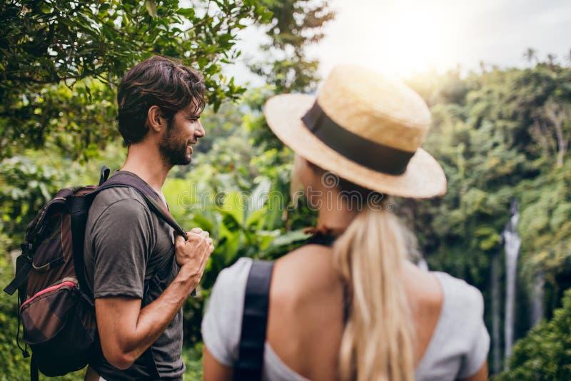 Νεαρός άνδρας που στέκεται με τη φίλη του στο δάσος στοκ εικόνες