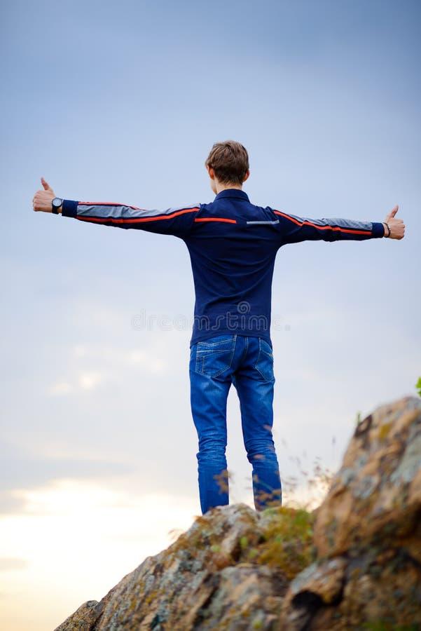 Νεαρός άνδρας που στέκεται στην αιχμή βουνών με τα όπλα που αυξάνεται Ενεργός έννοια τρόπου ζωής στοκ φωτογραφία με δικαίωμα ελεύθερης χρήσης