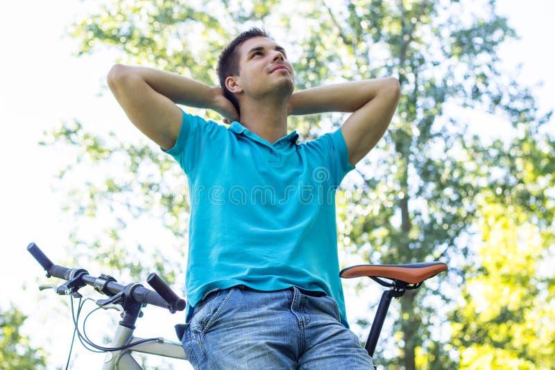 Νεαρός άνδρας που στηρίζεται μετά από έναν γύρο ποδηλάτων στοκ εικόνα με δικαίωμα ελεύθερης χρήσης