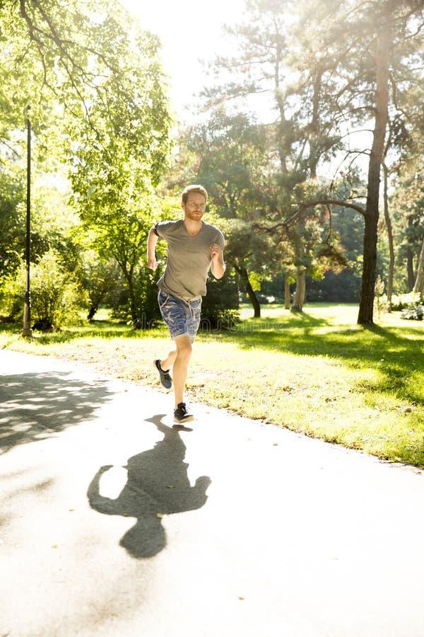 Νεαρός άνδρας που τρέχει στο πάρκο φθινοπώρου στοκ φωτογραφίες
