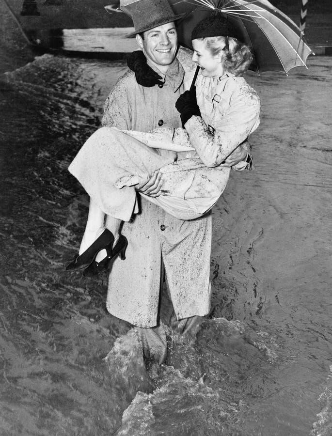 Νεαρός άνδρας που φέρνει μια γυναίκα μέσω μιας καταιγίδας (όλα τα πρόσωπα που απεικονίζονται δεν ζουν περισσότερο και κανένα κτήμ στοκ εικόνα