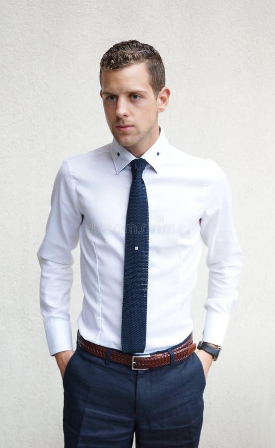 Νεαρός άνδρας που φορά ένα άσπρο πουκάμισο και έναν μπλε δεσμό στοκ εικόνες