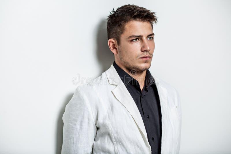 Νεαρός άνδρας που φορά το άσπρο κοστούμι στοκ εικόνες