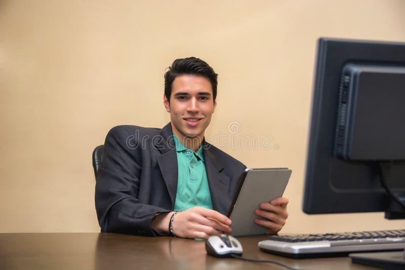 Νεαρός άνδρας που φορά το επιχειρησιακό κοστούμι στην αρχή με στοκ φωτογραφία