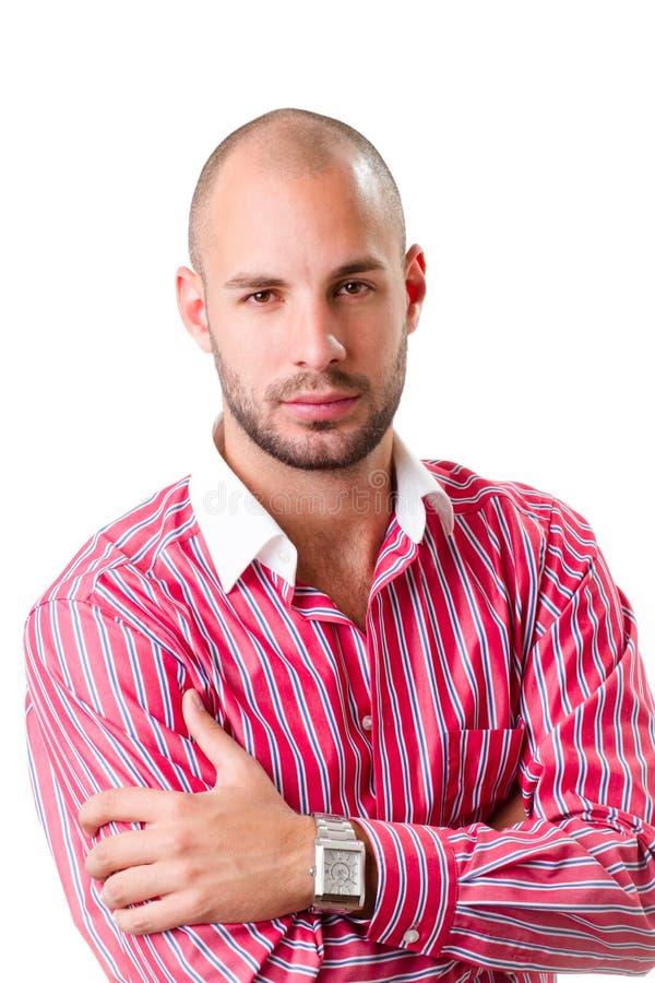 Νεαρός άνδρας που φορά το κόκκινο ριγωτό πουκάμισο και που εξετάζει τη κάμερα στοκ εικόνες